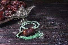 Grânulos de oração islâmicos verdes, datas e lâmpada de prata do ` s do aladdin em um fundo de madeira escuro Conceito da ramadã Fotos de Stock