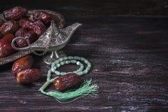 Grânulos de oração islâmicos verdes, datas e lâmpada de prata do ` s do aladdin em um fundo de madeira escuro Conceito da ramadã Imagens de Stock