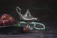 Grânulos de oração islâmicos verdes, datas e lâmpada de prata do ` s do aladdin em um fundo de madeira escuro Conceito da ramadã Fotos de Stock Royalty Free