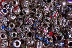 Grânulos de prata de formas diferentes com close-up colorido das pedras fotografia de stock royalty free