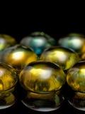 Grânulos de vidro amarelos no fundo preto fotos de stock royalty free