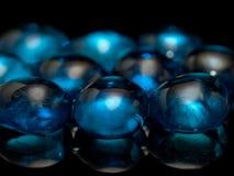 Grânulos de vidro azuis no fundo preto fotos de stock