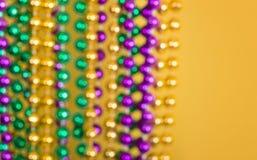 Grânulos Defocused de Mardi Gras contra o fundo amarelo foto de stock