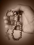 Grânulos do rosário da terra arrendada da mão Fotografia de Stock Royalty Free