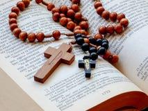 Grânulos do rosário na Bíblia Sagrada aberta Imagens de Stock