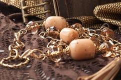 grânulos e corrente dourada perto da correia de couro no laço textured marrom fotos de stock