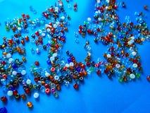 grânulos multi-coloridos em uma tela azul foto de stock
