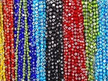 Grânulos que penduram em cores azuis, vermelhas, pretas, verdes fotografia de stock