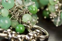 Grânulos verdes em um artigo da joia de prata fotos de stock
