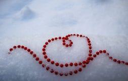 Grânulos vermelhos brilhantes na forma de um coração na neve branca fresca Dia de Valentim perfeito, Natal, fundo do cartão do an fotografia de stock