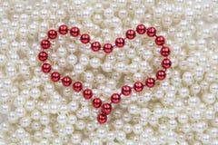 Grânulos vermelhos na forma de um coração Fotografia de Stock