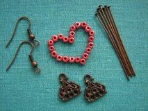 Grânulos vermelhos no formulário do coração, fazendo brincos, joia feito a mão fotografia de stock