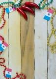Gr?nulos vermelhos, verdes e do ouro com bandeira mexicana e chilis vermelhos em um fundo de madeira Imagem vertical para Cinco d foto de stock