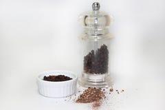 Grão de pimenta preto com o moinho no fundo branco foto de stock royalty free