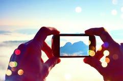Grão do filme A fotografia móvel do telefone esperto de montanhas rochosas ensolaradas ajardina Foco ao detalhe Imagens de Stock Royalty Free