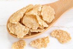 A grão inteira do trigo lasca-se na colher de madeira no backgrou de madeira branco fotografia de stock