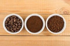 Grão, terra e café instantâneo nas bacias de vidro na tabela Fotos de Stock Royalty Free