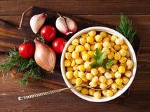Grãos-de-bico cozinhados na bacia na tabela de madeira escura Saudável, alimento nutritivo da proteína do vegetariano da opinião  fotografia de stock