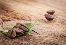 Grãos de café e folha verde no grunge de madeira imagens de stock royalty free