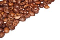 Grãos de café fritados em um fundo branco Macro Fotos de Stock