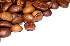 Grãos de café fritados em um fundo branco Macro Imagens de Stock