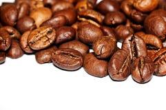 Grãos de café fritados em um fundo branco Macro Imagem de Stock Royalty Free