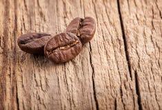 Grãos de café na placa de madeira velha fotografia de stock