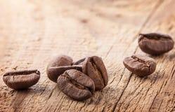 Grãos de café na tabela de madeira fotos de stock royalty free