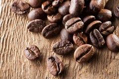 Grãos de café sobre a tabela de madeira Fotos de Stock