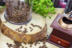 Grãos de café no corte da serra da árvore ao lado do moedor de café fotografia de stock royalty free
