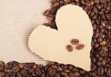 Grãos de café no papel o formulário do coração Imagem de Stock Royalty Free