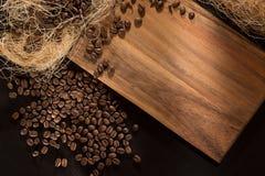 Grãos de café roasted preto Em um fundo de madeira Vista superior e quadro para inscrição Fotos de Stock Royalty Free