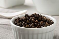 Grãos de pimenta crus, naturais, não processados da pimenta preta na bacia branca Imagem de Stock Royalty Free