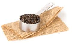 Grãos de pimenta crus, naturais, não processados da pimenta preta na medição Foto de Stock Royalty Free