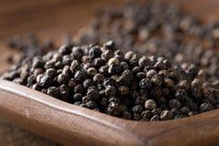 Grãos de pimenta crus, naturais, não processados da pimenta preta no pla de madeira Fotos de Stock