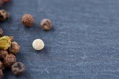 Grãos de pimenta crus, naturais, não processados macro no fundo escuro com foco seletivo, profundidade de campo rasa Fotografia de Stock