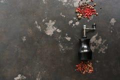 Grãos de pimenta e moinho de pimenta em um fundo rústico escuro Vista superior, configuração lisa, espaço para o texto foto de stock royalty free