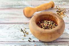 Grãos de pimenta em um almofariz na tabela de madeira clara Imagem de Stock