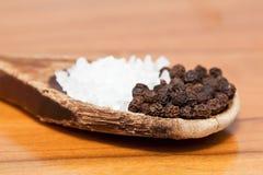 Grãos de sal grosseiro e de pimenta na colher de madeira Fotos de Stock Royalty Free