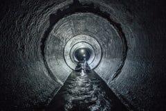 Gräber erforschen den Untertagefluß, der in runden Abwasserkanaltunnel fließt Lizenzfreie Stockfotos