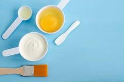 Gräddfil- eller grekyoghurt, rått ägg och olivolja i små skopor Ingredienser för att förbereda diy maskeringar, skurar, fuktighet Arkivbild