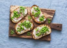 Gräddost, gröna ärtor, rädisor och mikrogräsplaner fjädrar smörgåsar på en skärbräda Sunt äta som bantar, bantar livsstil Arkivbild