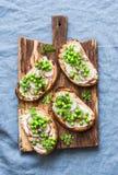Gräddost, gröna ärtor, rädisor och mikrogräsplaner fjädrar smörgåsar på en skärbräda Sunt äta som bantar, bantar livsstil Arkivfoton