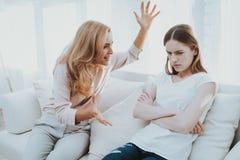Gräla mellan modern och dottern i vitt rum arkivfoto