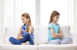 Grälade små flickor som hemma sitter på soffan royaltyfri bild