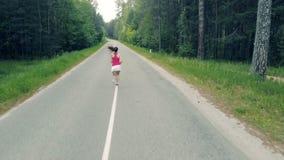 Gränd i skogen med en nätt dam som joggar längs den _ stock video