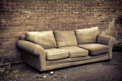 gränd kasserad gammal sofa Royaltyfri Bild