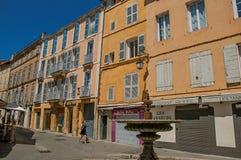 Gränd med byggnader, kvinnan och springbrunnen i Aix-en-provence Arkivfoton