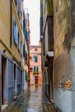 Gränd mellan gotiska stilbyggnader på tegelsten/kullerstengatan i Venedig, Italien fotografering för bildbyråer