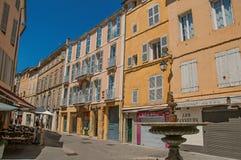 Gränden med färgrika byggnader, shoppar och springbrunnen i Aix-en-provence Arkivfoton